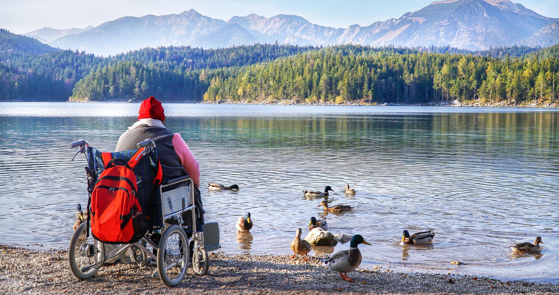 Anziano in carrozzella che guarda il lago