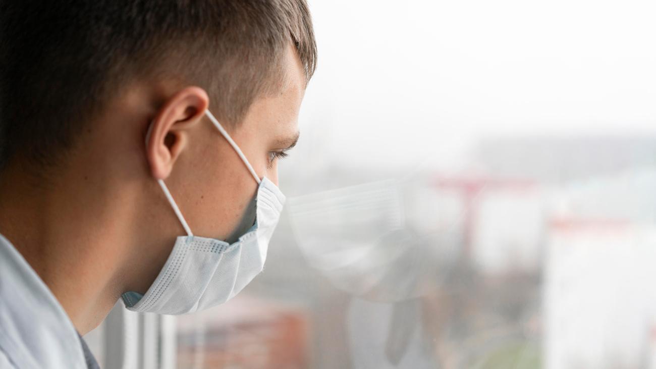 Un uomo con una mascherina osserva pensieroso fuori dalla finestra