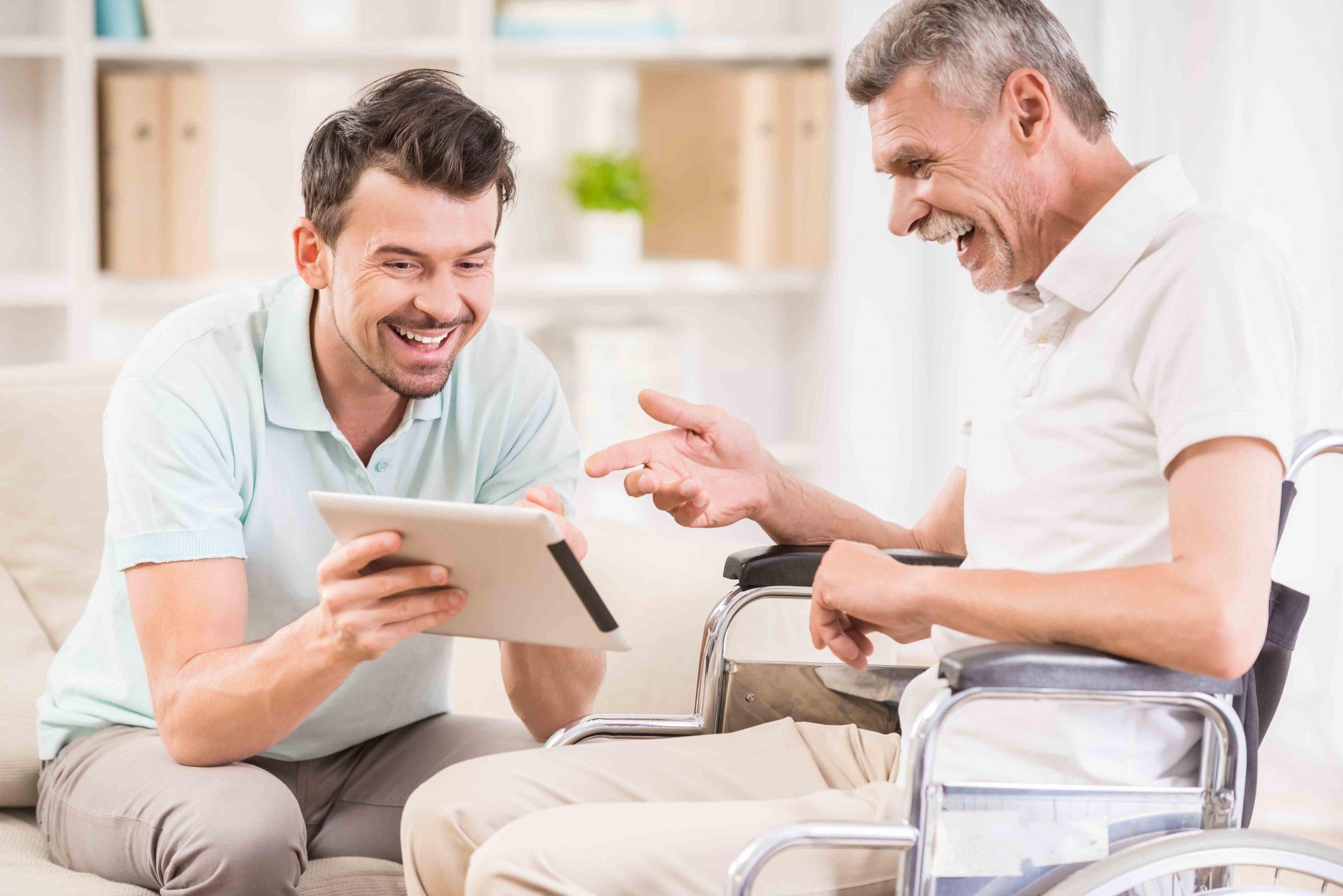 Un uomo in carrozzina e il suo caregiver si divertono guardando una foto