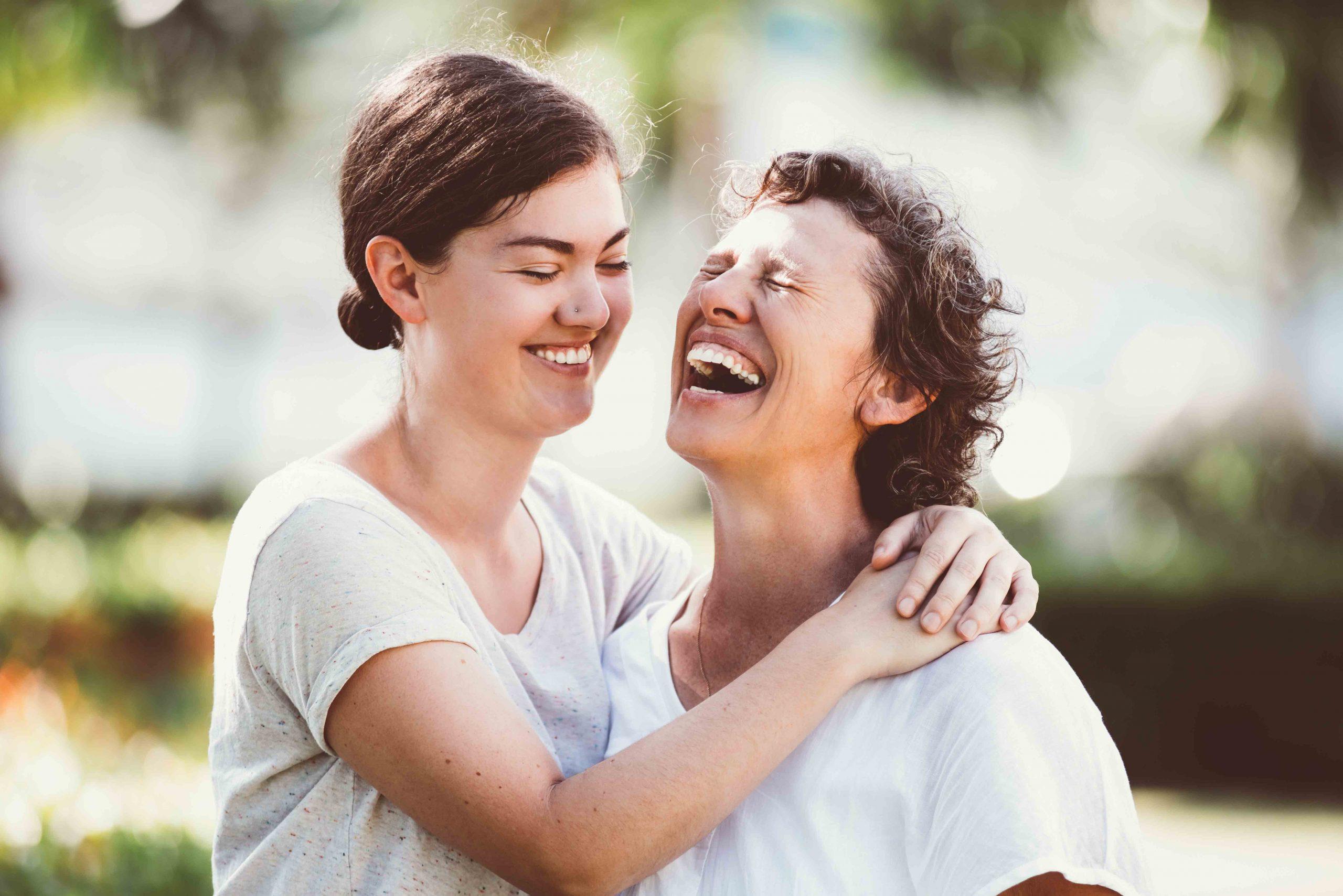 Due donne che si abbracciano ridono allegramente