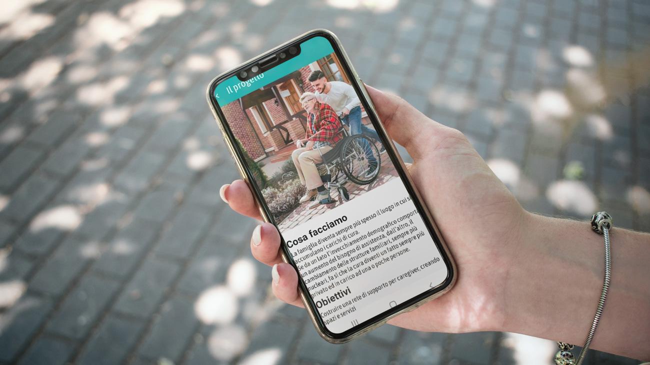 Una persona tiene in mando uno smartphone con l'anteprima dell'app di rete Caregiver