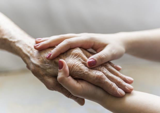La mano di una giovane donna stringe quelle di un'anziano